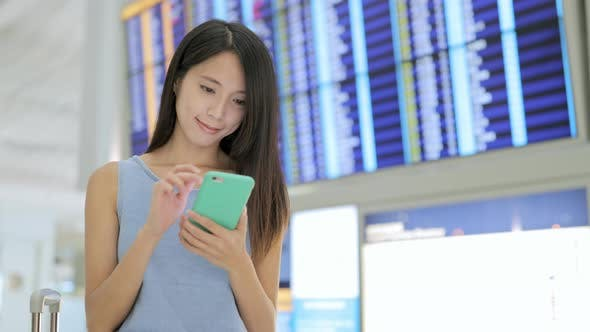 Thumbnail for Woman use cellphone to check the flight number in airport