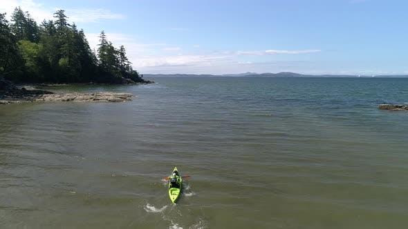 Thumbnail for Rising Aerial Of Man Paddling Kayak Out To Sea Slow Motion