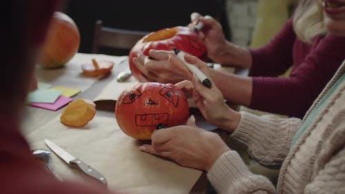 An Elderly Woman Shows a Man a Halloween Pumpkin She Made Herself