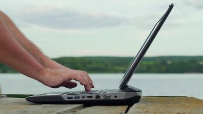 Man's hands using laptop computer. Young man using laptop on the pier.