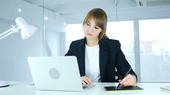 Female Designer working with Drawing tablet on Laptop