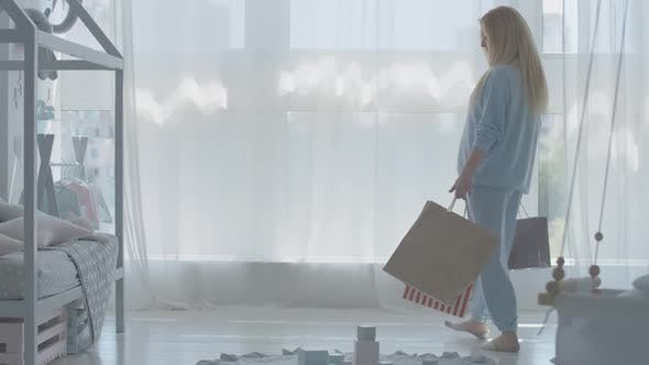 Thumbnail for Pregnant Woman Entering Baby Room with Shopping Bags and Sighing. Beautiful Young Caucasian Lady