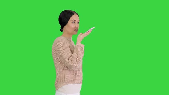 Thumbnail for Young Woman Talking on the Phone Holding It To Her Face While Walking on a Green Screen, Chroma Key.