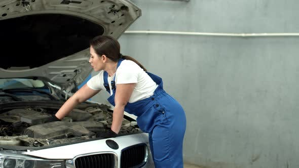 Woman Mechanic Repairs a Car in Car Service