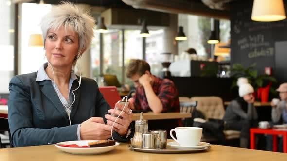 Thumbnail for Middle Aged Woman Listens Music in Cafe (Earphone) on Smartphone