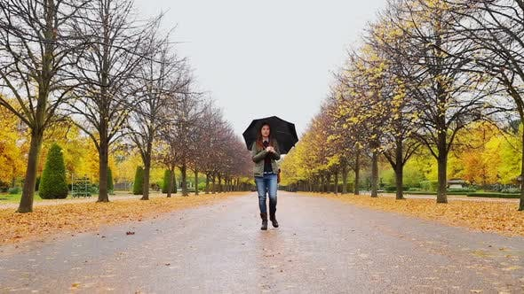 Thumbnail for Woman walking with umbrella in park