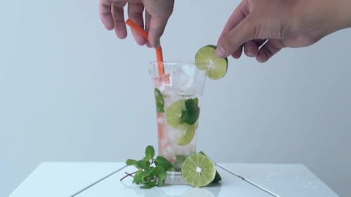 Man Takes Out Straw and Lime Slice From Glass on White Table