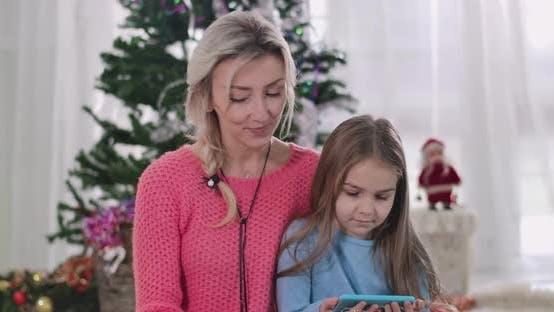 Thumbnail for Nahaufnahme der jungen kaukasischen Mutter beobachten Film oder Cartoon mit Tochter auf Smartphone-Bildschirm
