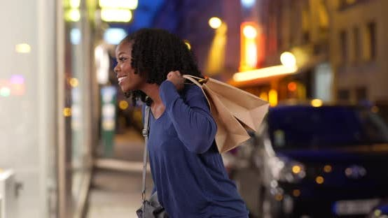Thumbnail for Cute smiling black female walks over to look at window display in Paris at night