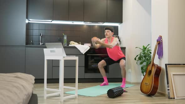 Funny man athlete in pink top doing squats watching online fitness classes on notebook at home