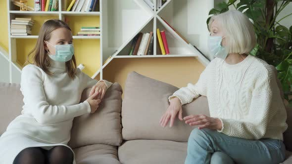 Thumbnail for Daughter and Senior Mother Wearing Medical Masks Having Fun Talk at Home, Elderly Millennial Women