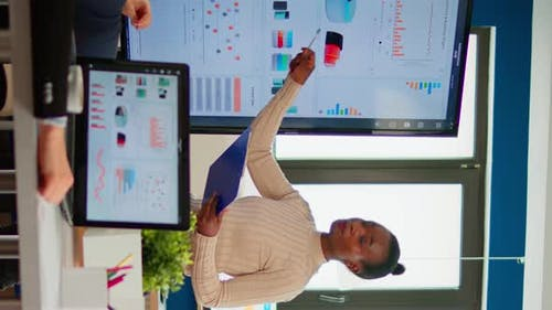 Black Woman Worker Explaning Company Statistics in Front of Colleagues