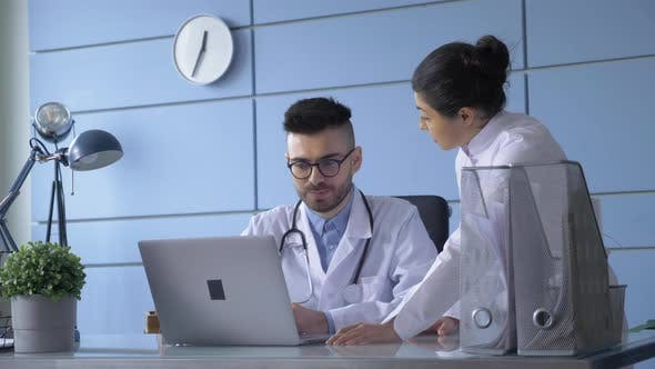 A Portrait Of Man And Woman Doctor With Laptop Sitting In Hospital Office.