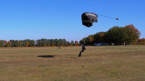 Skydiver Flying with a Parachute and Landed on the Ground. Slow Motion