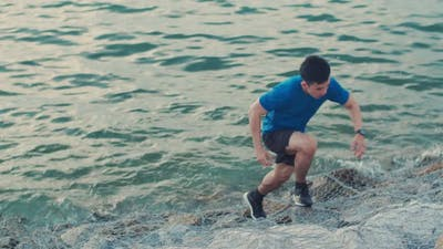 Male runner sprinting trying upon the rock at the seaside.