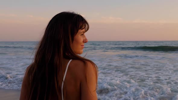 Thumbnail for Beautiful woman in a white dress at the beach at sunset