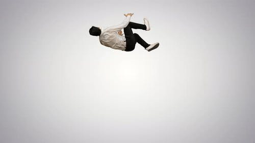 Young Man Dressed in White Shirt and Black Pants Dancing Break-dance and Smiling at Camera at the