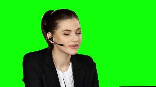 Cover Image for Female Receptionist Working on Computer and Talking on the Telephone in Call Center, Green Screen