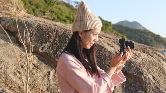 Thumbnail for Woman taking photo on camera in the countryside