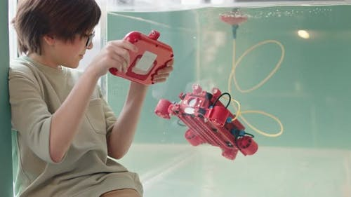 Caucasian Boy Playing with Robo Boat