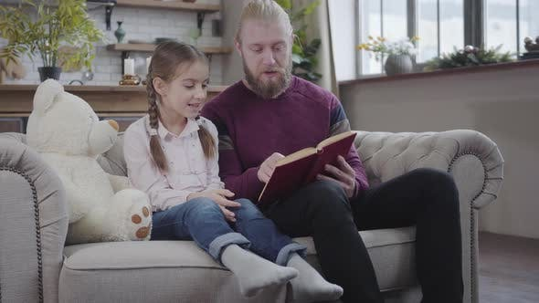 Cover Image for Portrait of Intelligent Young Father Reading To His Lovely Daughter. Interested Teen Girl Listening