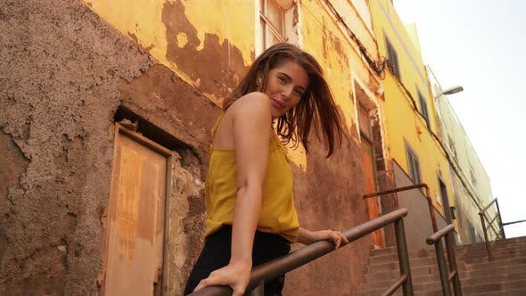 Beautiful Model on the Steps of Stairs Smiling While Holding on Rails