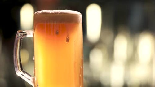 Glass of Beer Rotating and Overflowing
