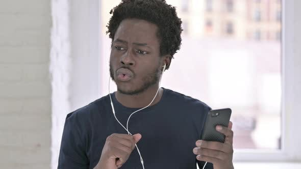 Cover Image for Portrait of Young African American Man Listening Music with Head Phones