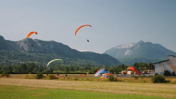 Orange paragliders going on landing at landing strip in Alps mountains