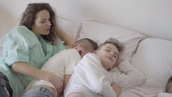 Cover Image for Portrait Young Mother with Her Teen Sons Sleeping Together in the Big Bed