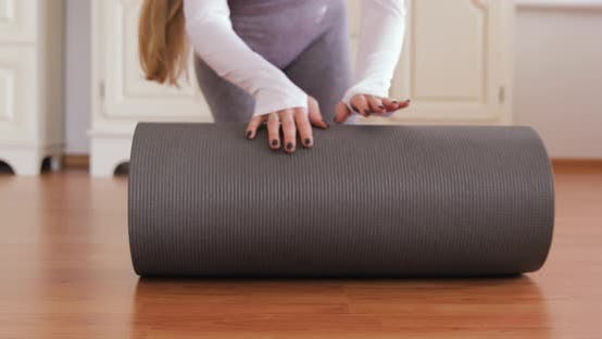 Thumbnail for 5 D4 Close-up of attractive white woman rolling out her red and grey yoga mat. health care concept