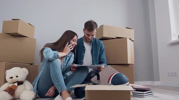 Thumbnail for Couple Sitting on the Parquet Among Many Boxes and Looking at Pictures with Design