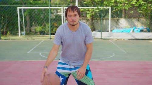 Ein Mann stehend auf einem Sportplatz und hält einen Basketballball