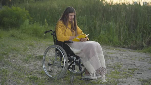 Thumbnail for Wide Shot of Smiling Disabled Woman Reading Outdoors at Sunset. Portrait of Young Beautiful