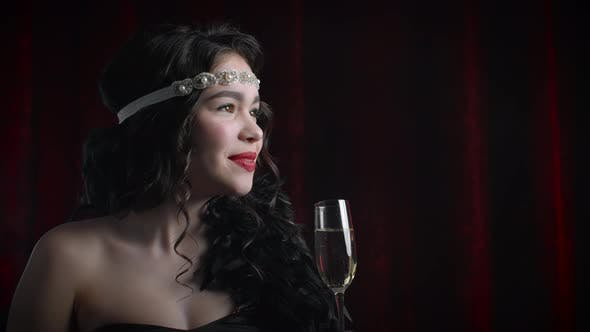 Thumbnail for Portrait of Vintage Styled Woman Dressed in Great Gatsby Era Drinking Champagne