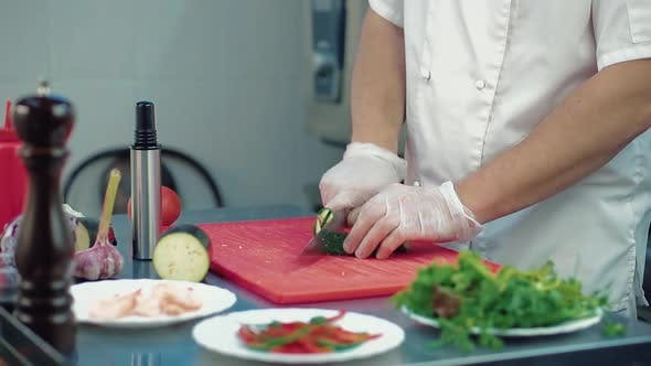 Cook Cuts a Fresh Cucumber for a Salad with a Knife