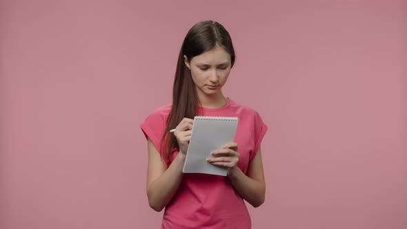 Portrait of Fashion Model is Thinking and Writing Down Her Ideas in Notebook