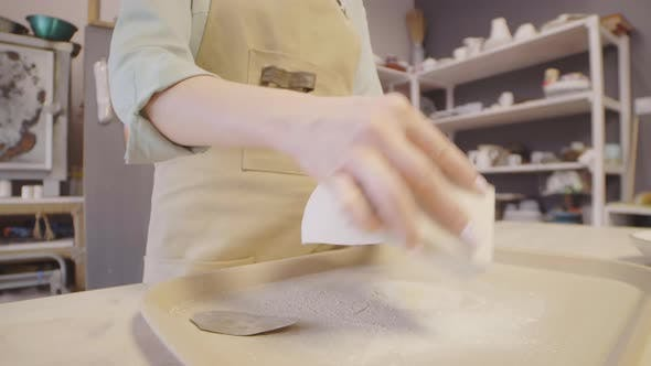 Unrecognizable Female Artisan Sanding Handcrafted Clay Dish