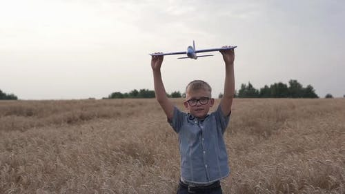 Happy guy with a toy airplane on a wheat field in the sunset light.