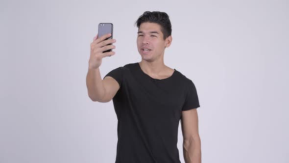 Thumbnail for Happy Young Handsome Multi-ethnic Man Video Calling and Showing Phone