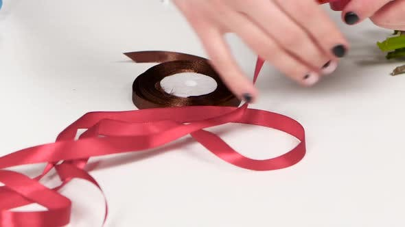 Thumbnail for Holiday Decorations. Hand Pick Up Pink Ribbon From Table. White. Close Up
