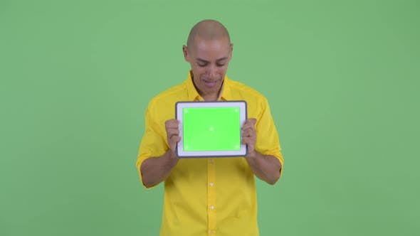 Thumbnail for Happy Handsome Bald Businessman Showing Digital Tablet and Looking Surprised
