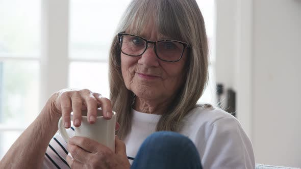 Portrait of senior Caucasian woman holding coffee cup and looking at camera