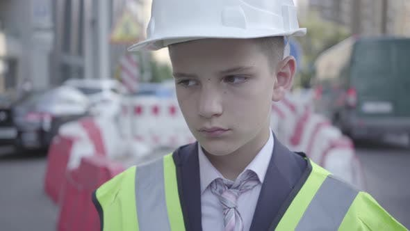Thumbnail for Portrait of Sad Tired Little Boy in Constructor Helmet on His Head, and Uniform Looking Away