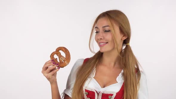 Thumbnail for Sexy Bavarian Woman Licking Her Lips, Looking at Delicious Pretzel