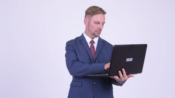 Thumbnail for Happy Blonde Businessman Thinking While Using Laptop