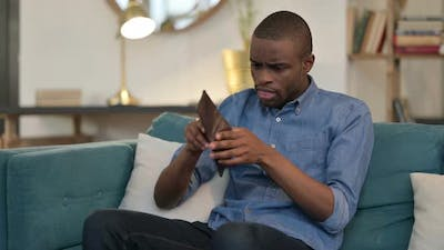 Broke Young African Man Checking Empty Wallet on Sofa