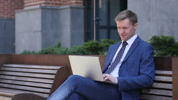 Thumbnail for Excited Businessman Celebrating Success, Working on Laptop