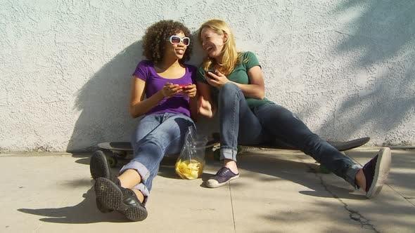Thumbnail for Two women friends sitting on skateboards