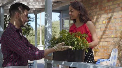 Young Smiling Bearded Farmer Discussing Flowers with Attractive Young Woman
